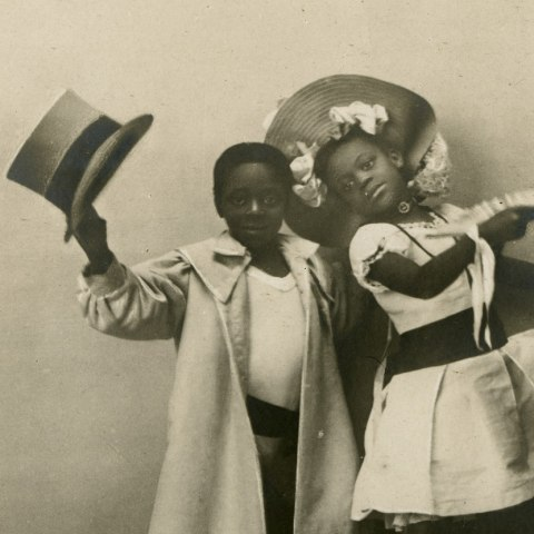 Postcard with photo of two young children wearing ballet shoes. Little boy holds top hat in his raised hand and an over-sized coat. The little girl strikes a pose with a fancy fan and wears a full-skirted tea length dress and a hat with many bows.