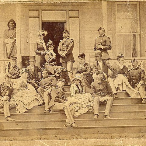 An old photograph in sepia tones showing a number of people sitting on stairs outside of a building. Some are women and some are men, many of whom are wearing uniforms.
