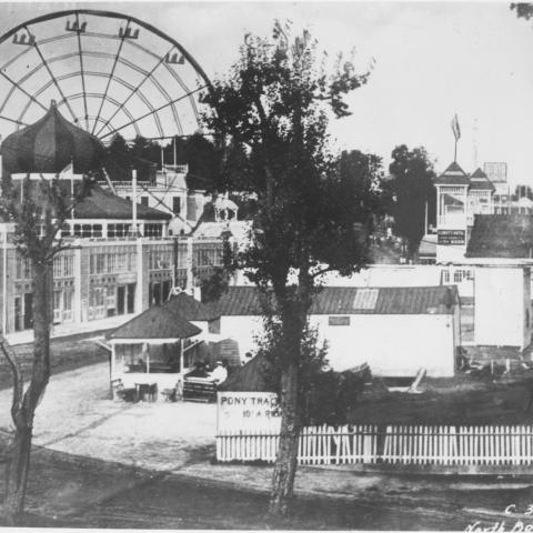 Black-and-white photo of pony tracks, buildings, ferris wheel