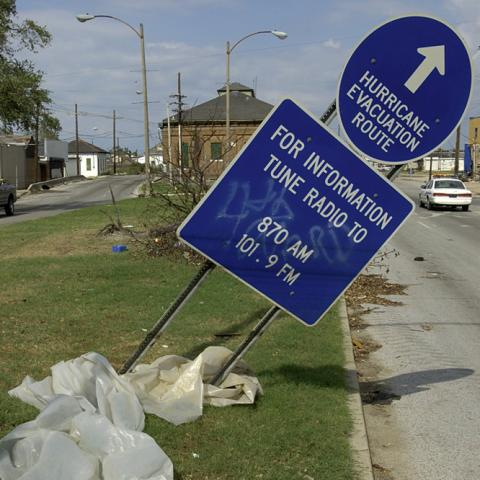 """Titled sign, knocked over half way. Blue circular sign with arrow saying """"HURRICANE EVACUATION ROUTE."""" Below that is square sign with AM FM radio stations for information. There is a dirty plastic bag on the ground."""