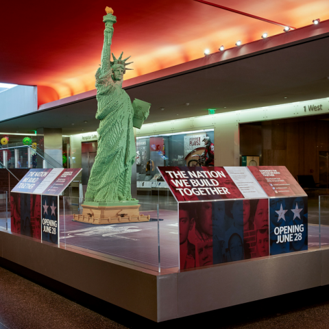 A lobby with glass cases of objects and a stairway. The ceiling is a lurid red. In the center is a lego statue resembling the statue of liberty, resting on a large rectangular display with short glass walls surrounding it that have signage on it.