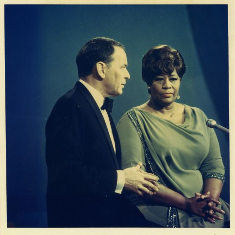 Frank Sinatra and Ella Fitzgerald sit in front of a microphone