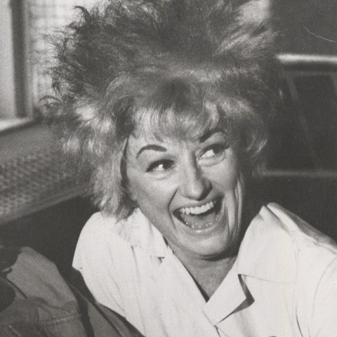 In a black and white photograph a woman in a white collared shirt and hair sticking up in every direction is laughing