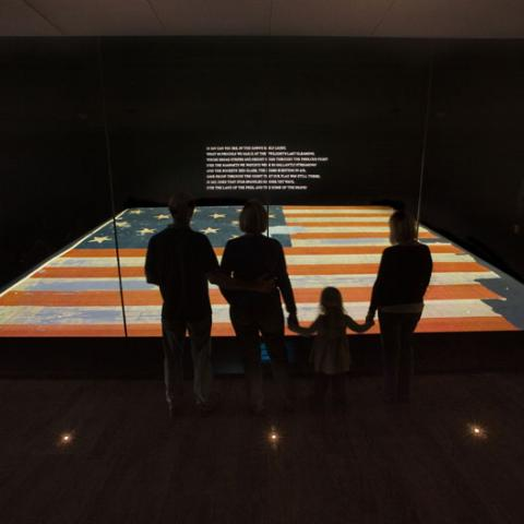 Museum visitos look at the Star Spangled Banner