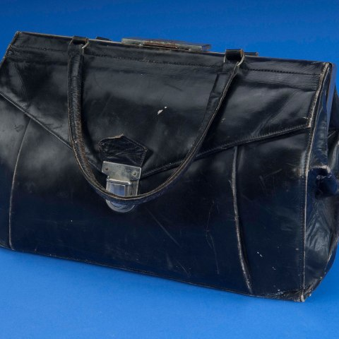 Photo of a black purse with a short handle. It is rectangular and bulges in the middle as though it's full. A little worn around the edges. Metal buckle.