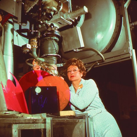 Photo of woman with short curly hair, blue dress, and large equipment