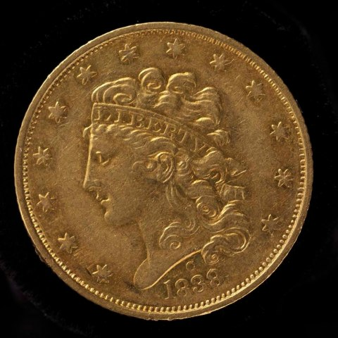 "Gold coin marked 1838 decorated with stars and the profile of Liberty's head. Liberty wears a head-band that reads ""Liberty."""