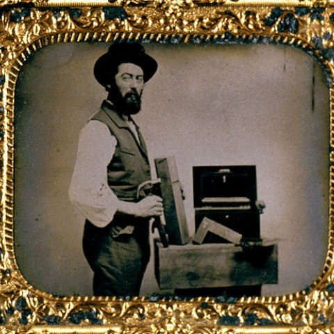 Gold frame containing black and white photo of man in hat showing off some type of instrument in box