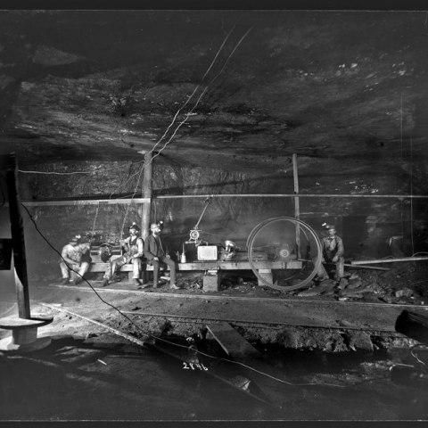 Photograph of miners posing around dynamo, around 1884