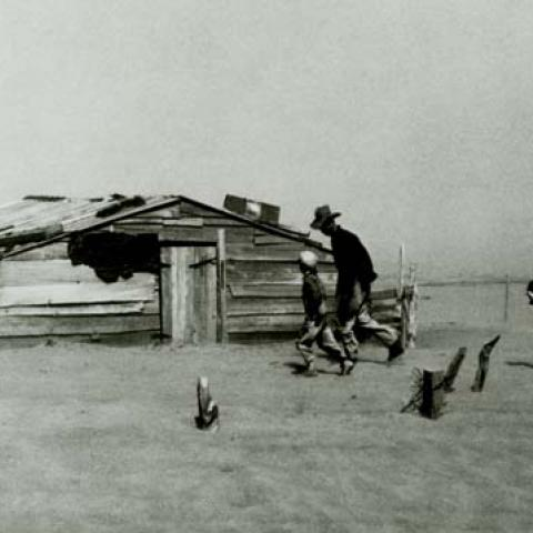 Dust Bowl photo with wooden house and people running for cover