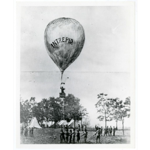 People watch a Civil War balloon go up above a treeline