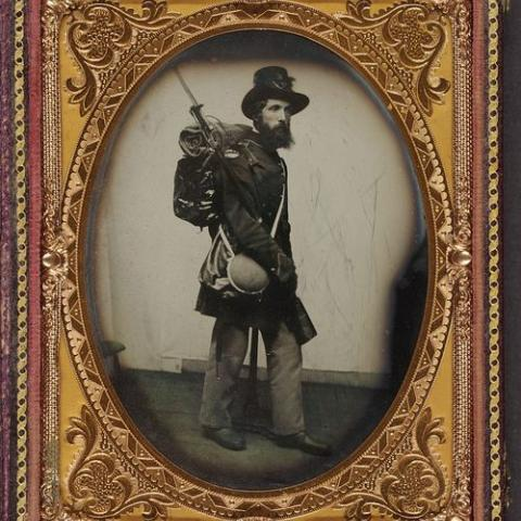 This photograph shows Private Albert H. Davis of Company K, 6th New Hampshire Infantry in his uniform, equipped with a knapsack, bedroll, canteen, and haversack. Very elaborate frame!