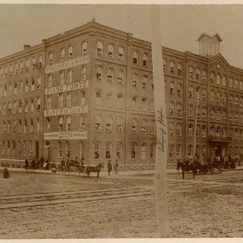 Photograph of a street corner with a large building and horse carriages
