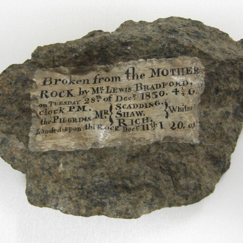 a rock with lettering describing the date, location, and men present