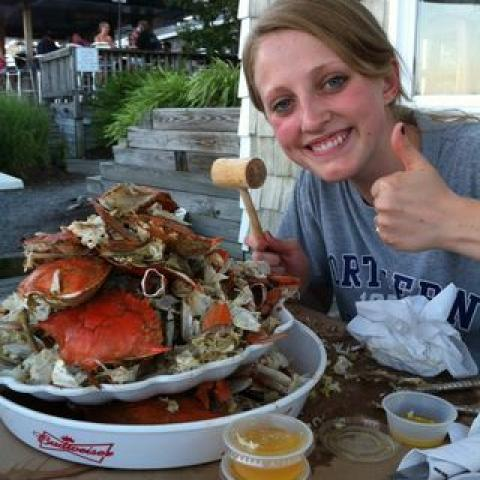 Young female intern with the remnants of a crab feast, including containers of butter, napkins, crabs, in an outdoor setting