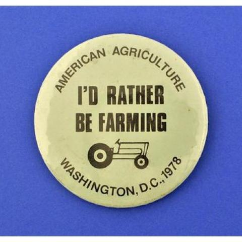 """White button that says """"I'd rather be farming"""" in black text with the image of a tractor"""