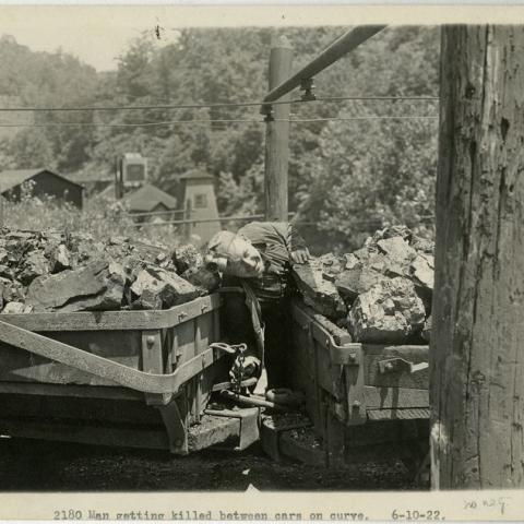 Staged photograph of a man re-enacting a mining accident. The man is posed as if he has been pinned between to loaded train cars making a sharp curve on the tracks.