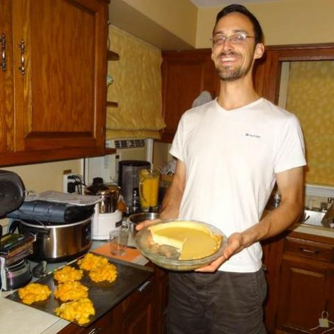 A thin man holds a yellow-colored pie in a kitchen