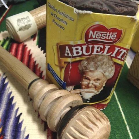 Container of Abuelita hot chocolate on colorful fabric
