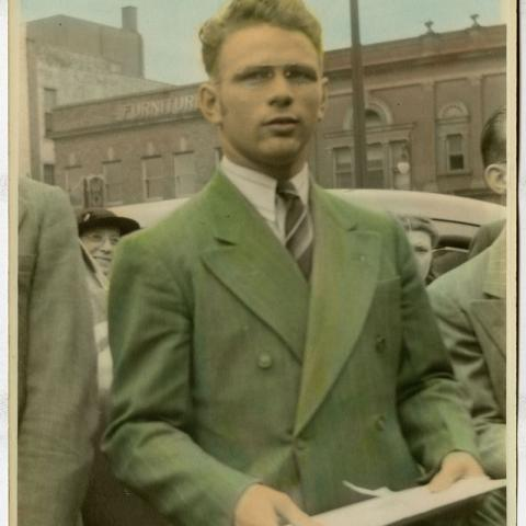 Photograph of man in a suit on the street with glasses
