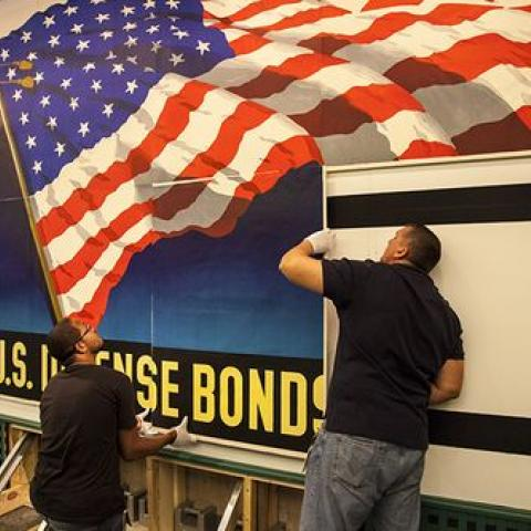 Two men secure the billboard which includes a large flag image