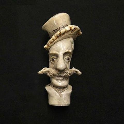 This umbrella handle, 4 ½ inches long and carved from horn, was collected in 1875 as an example of material manufacturing. It features a narrow face with a mustache.