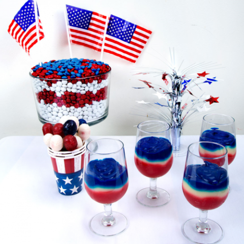 Red, white, and blue food (puddings, candies, lollipops) displayed on a table