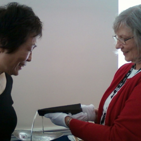 One woman looks at Abraham Lincoln's wedge tool while another holds it