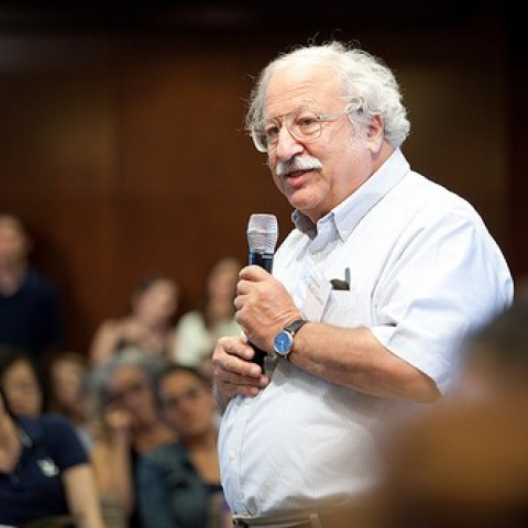 Ganz holding microphone speaking to audience, wearing white shirt