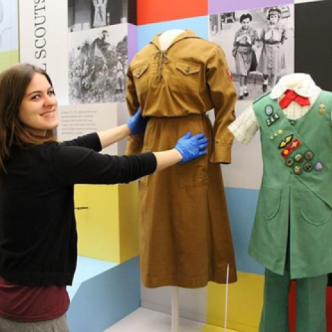 Female staff member wearing blue gloves prepares to remove a brown Girl Scout uniform from an exhibition case
