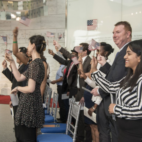 Official U.S. citizens with their certificates in hand, waving their flags