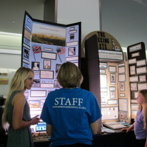 Museum staff and students look at a National History Day project on a large board