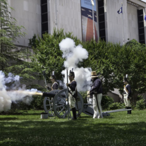 War of 1812 re-enactors in white and blue uniforms fire a canon in front of the museum