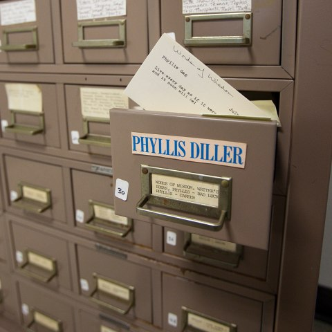 "A view of a brown filing cabinet. One drawer is pulled out slightly with the label ""Phyllis Diller"" and a small metal handle with an ID card stuck inside. A small note card with typed script is pulled out slightly."