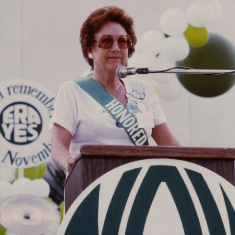 "Jean Stapleton stands at a podium addressing the crowd wearing a banner that says ""Honored."" A sign behind her reads: ""ERA Yes"""