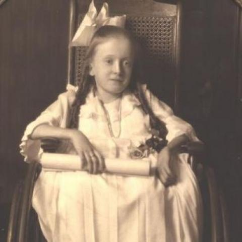 Black and white portrait of small girl with large white bow in her hair, holding rolled paper in hand, sitting in wheel chair
