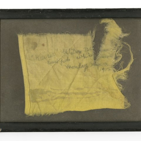 Yellow scrap of fabric in a frame. Pencil writing on fabric.