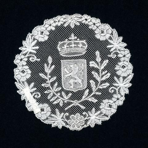 Photo of white lace in the shape of a circle with lion and crown in center