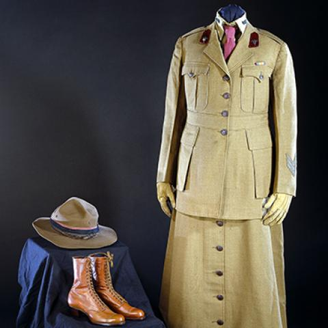 Khaki uniform with skirt and collared jacket. Large brown buttons and two breast pockets. Brown lace-up boots with small heel. Brown hate with ribbon around it.