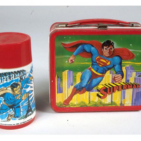 """This tin lunch box was manufactured by Aladdin Industries in 1978. Released on the heels of the 1978 """"Superman"""" movie, this lunch box shows Superman flying high above Metropolis in all his costumed glory. Not currently on display."""