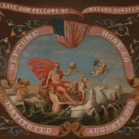 """An illustration showing a cluster of figures. Neptune rides some sort of chariot pulled by four horse, with sea nymphs surrounding him and a cupid flying in the air. The scene is framed by pink ribbons saying """"Neptune Hose Co.  Instituted August 6, 1805 and banners reading """"To save out fellows we hazard ourselves"""""""