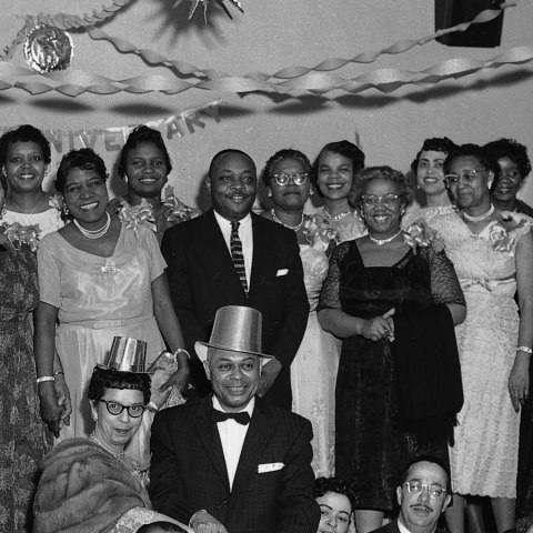 (Detail) Many people in formal outfits sit at a long table with a white tablecloth. A couple smiles, wearing silly hats, about to cut a cake. Behind them, 15 or 16 people stand on a raised platform or stage, smiling for the photo. Streamers and other decorations are visible on the ceiling. There are tall candles in candle holders on some of the tables.