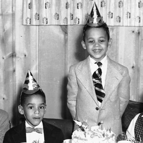 (Detail) Indoor black and white photo of children gathered around a rectangular table, wearing party hats and waiting to eat cake. The birthday boy, in suit and tie, grins, standing with his hands behind his back with his two-tiered cake in front of him. Behind him, a patterned curtain. Wood-paneled room.