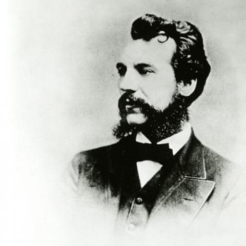 Black and white portrait of bearded young-ish man from shoulders up, looking left.