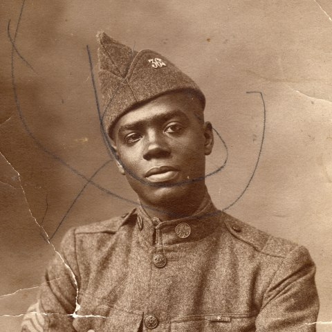 (Detail image) Black and white photo of an African American man in military uniform. His arms are gently crossed, a watch o his wrist. His head is slightly tilted to the right, with a serious but gentle look on his face. The uniform has pockets, buttons, and a fairly high collar.