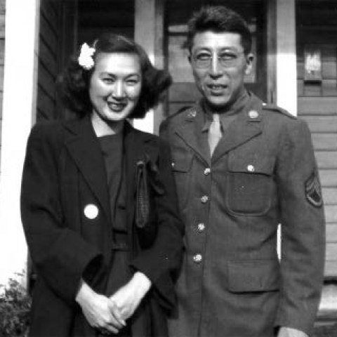 A man in a military uniform and a woman in a dark coat stand smiling in front of a house.