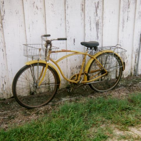 Yellow bike with front and back baskets leans against a worn white wall, in the grass.