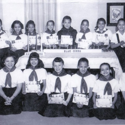 Girls in uniform sit around a table holding their certificates.