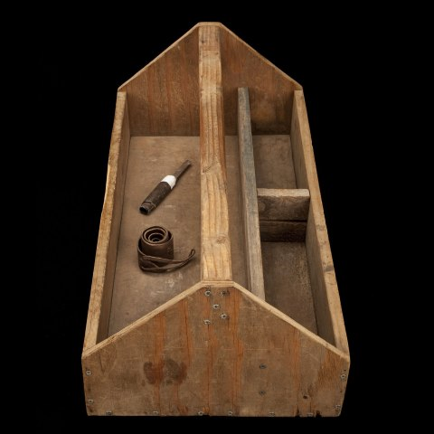 Photograph of wooden box. The box has a wooden handle in the middle and a space for tools. Inside, there are two tools.