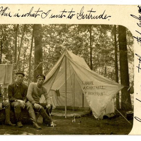 Black and white photo of three men sitting beside a white cloth tent in the woods